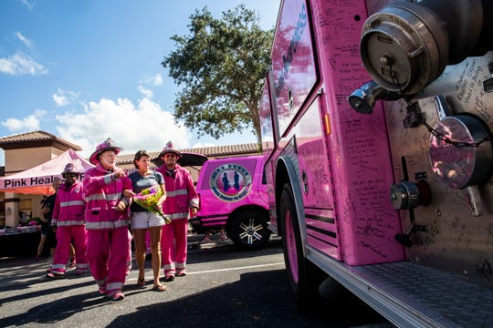 Don Hayworth, a driver for the national chapter of Pink Heals, leads Tricia Leckbee to sign their firetruck during a surprise fundraiser organized by her friends, family and coworkers with the nonprofit organization in front of Aerie Lane in Bonita Springs on Thursday, Oct. 18, 2018.
