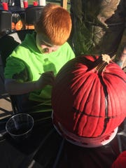 Christopher Bush, age 7, begins detailing his painted pumpkin at the Oct. 18 community event.