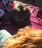 """At the """"Monster Pumpkin"""" table, a gourd gets a coat of black paint Oct. 18 in Freedom Park."""