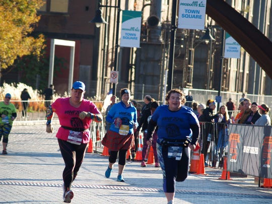 Jennie Coughlin, right, and Amy Wapnitsky finish the Runner's World 5K in Bethlehem, Pennsylvania, just a few weeks before Coughlin cheered for Amy's husband, Larry, during the 2016 NYC Marathon.