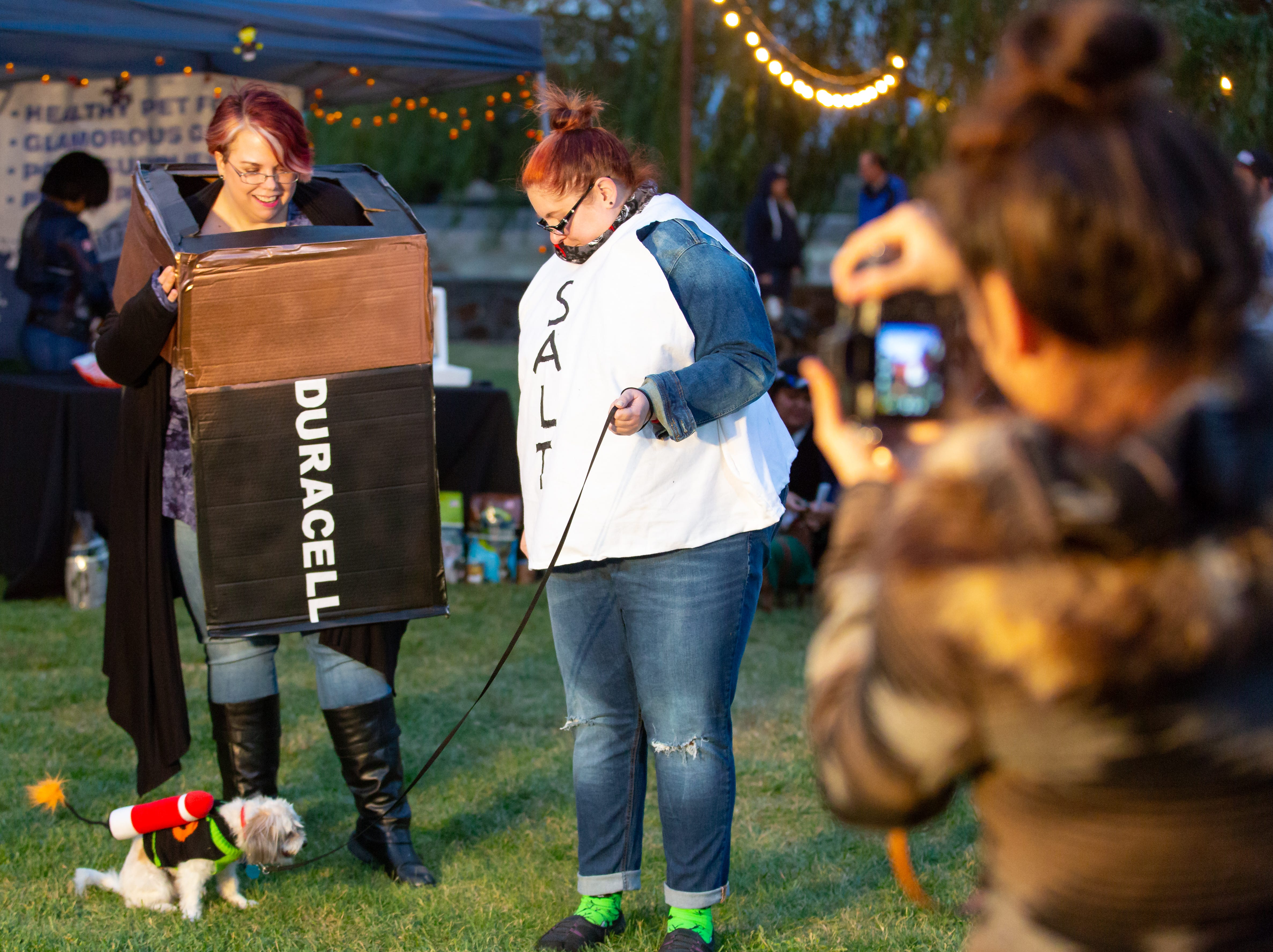 """While preforming under the stage name, """"Battery and Assault with a Deadly Weapon,"""" Rachael and Morgan Snow, sisters, show off their dog Jack at the Halloween costume contest for pets on Wednesday, Oct. 17, 2018, during the final Yappy Hour of the year at St. Clair Winery and Bistro."""
