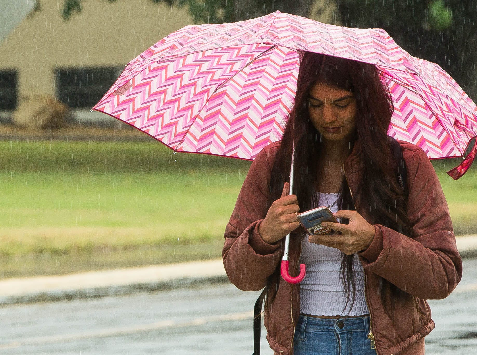 Destiny Lara, a student at New Mexico State University, walks to her car through the rain, Thursday October 18, 2018. The area continued to be blanketed in clouds, with sporadic showers through out the day.