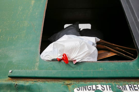 A plastic bag containing recyclables is deposited inside a recycling bin Thursday at the Waste Management recycling site in Farmington.