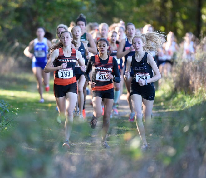 Northville's Nicole Cybul (left), teammate Yasmine Mansi (middle) and Plymouth's Lauren Kiley (right) battle it out in the lead pack at the KLAA girls cross country meet on Oct. 18 at Huron Meadows Metropark.