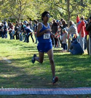 Salem's Talha Syed crosses the finish line of the 2018 KLAA conference cross country meet run Oct. 18 at Huron Meadows Metropark.