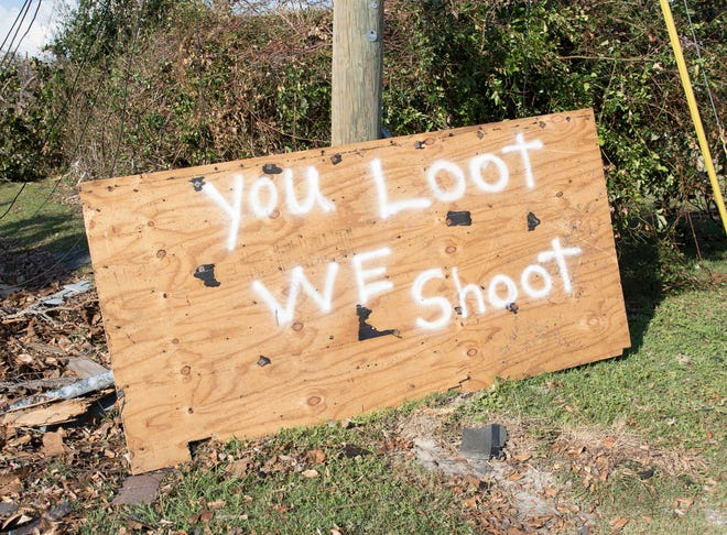 Signs warning against looting dot Panama City in the wake of Hurricane Michael on Wednesday, Oct. 17, 2018.