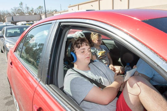 Casey McGraw, 16, watches videos on his smart phone while waiting in line for gas with his sister Jayla, 12, and grandmother Pat McDaniel after Hurricane Michael in Panama City, Florida on Wednesday, October 17, 2018.  Casey downloaded a bunch of videos from online prior to the storm to keep him entertained which is good since he currently doesn't have access to the web.
