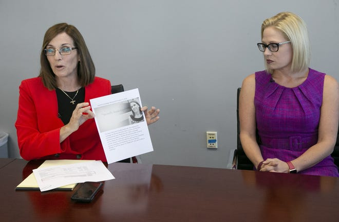 Republican Martha McSally (left) who is vying for a U.S. Senate seat for Arizona against Democrat Kyrsten Sinema, speaks with The Arizona Republic editorial board and Arizona Republic reporters while holding a printout of what she alleges is a Sinema attack ad against her, as Sinema looks on at The Arizona Republic in Phoenix on Wednesday, October 17, 2018.