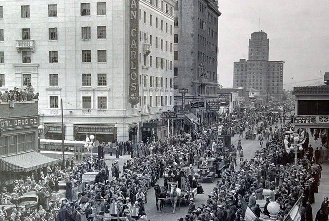 Spectators gathered to watch a parade along Central Avenue in Phoenix in 1937. This view is looking north from Adams Street toward the San Carlos Hotel and Hotel Westward Ho.