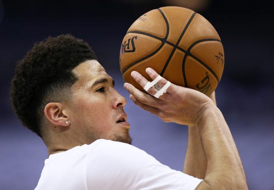 Suns guard Devin Booker warms up with tape on his right hand before a game against the Mavericks on Wednesday at Talking Stick Resort Arena.