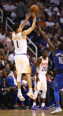 Devin Booker makes a three-point shot during the Suns' season opening victory over the Mavericks at Talking Stick Resort Arena.