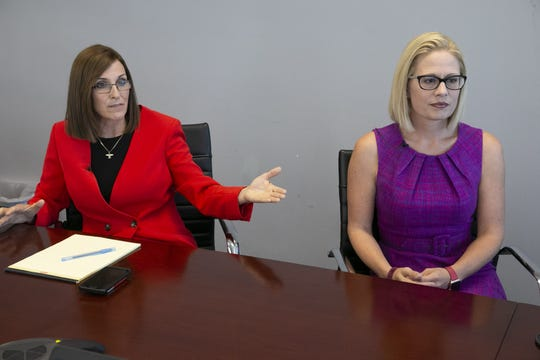 Republican Martha McSally,  left, who is vying for a U.S. Senate seat for Arizona against Democrat Kyrsten Sinema, speaks in Phoenix with the Arizona Republic editorial board and reporters as Sinema looks on Wednesday, Oct. 17, 2018.