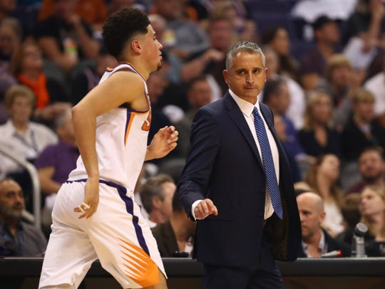 Suns coach Igor Kokoskov checks in with guard Devin Booker as he runs the floor during a game against the Mavericks.