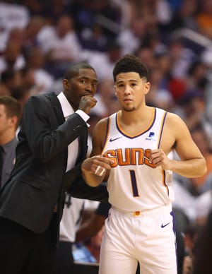 Veteran Jamal Crawford talks with Devin Booker (1) during the Suns' season opener against the Mavericks.