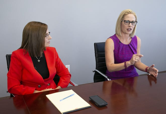 Democrat Kyrsten Sinema, (right) who is vying for a U.S. Senate seat for Arizona against Republican Martha McSally, speaks with the Arizona Republic editorial board and Arizona Republic reporters as McSally looks on at the Arizona Republic in Phoenix on Wednesday, October 17, 2018.