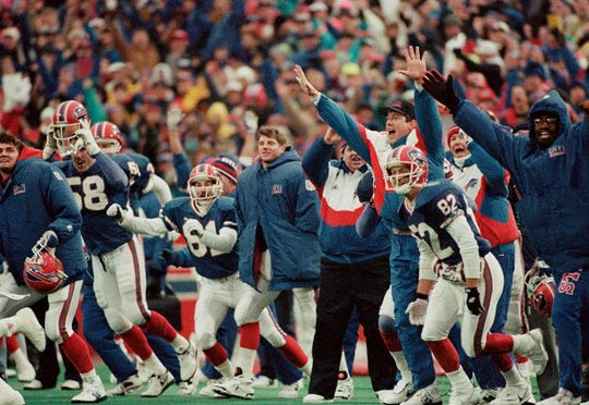 The Buffalo Bills bench, including receiver Don Beebe (82) and injured quarterback Jim Kelly, behind Beebe and wearing street clothes, celebrate Steve Christie's winning overtime field goal to beat the Houston Oilers 41-38, on Jan. 3, 1993, at Orchard Park.