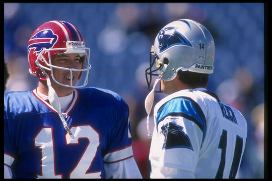 Bills quarterback Jim Kelly catches up with Carolina Panthers quarterback Frank Reich during a 1995 game at Rich Stadium.