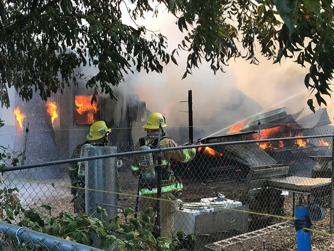 """Firefighters spray water on a fire burning at what was reported as a """"large shop"""" at 19509 Jacqueline St., Anderson."""