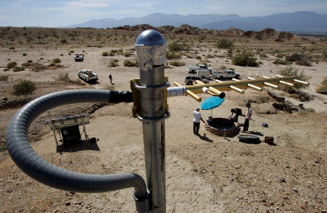 An antenna to send data stands on a rise above an earthquake monitoring well, right, powered by a solar electric panel, lower left, as scientists from the U.S. Geological Survey set up an earthquake monitoring station on the San Andreas Fault in a desert canyon near Thermal, Calif.