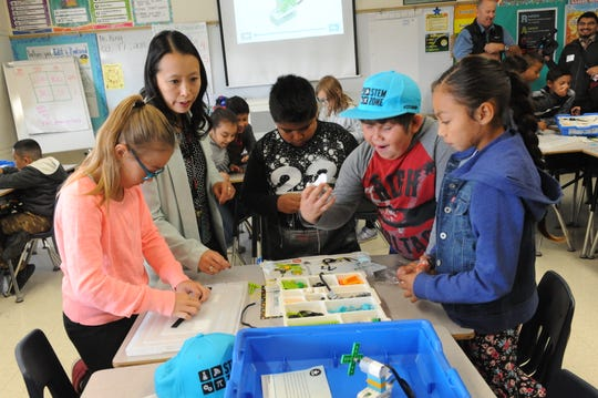 Lesley Kong helps her fourth grade students as they worked together on their new LEGO STEM kits on Wednesday.