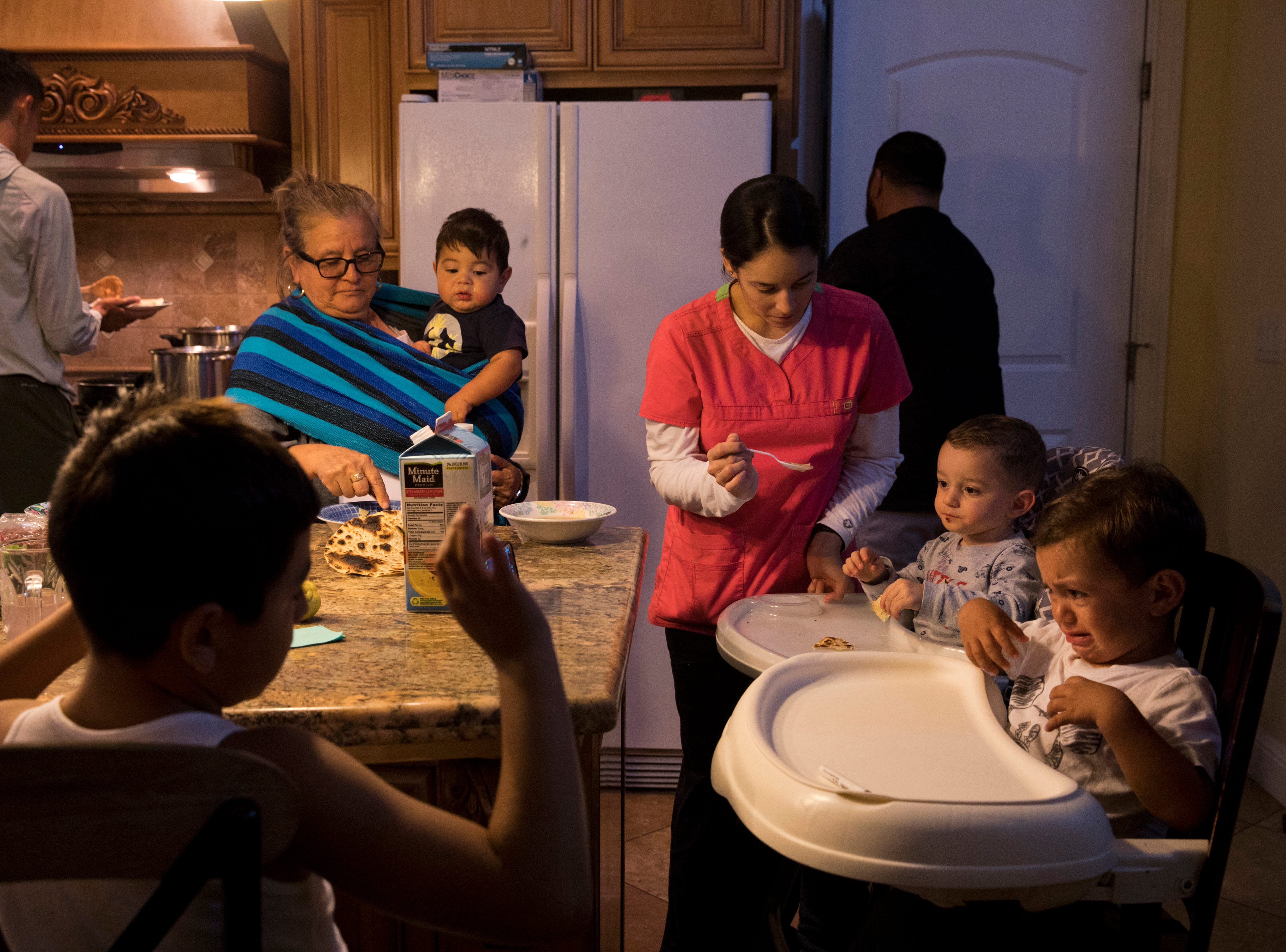 In this Thursday, Sept. 6, 2018, photo, Lilia Coyt, center left, and Coyt's daughter-in-law, Araceli Nunez, feed babies in their four-bedroom home, where three generations and 15 members of the family are jammed into, in Salinas, Calif. Few cities exemplify California's housing crisis better than Salinas, an hour's drive from Silicon Valley and surrounded by farm fields. It's one of America's most unaffordable places to live, and many residents believe politicians lack a grip on the reality of the region's housing crisis. (AP Photo/Jae C. Hong)