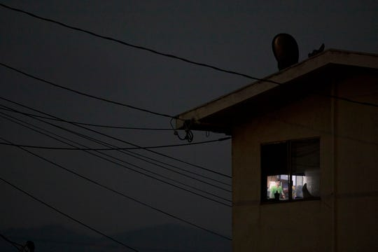In this Thursday, Sept. 6, 2018, photo, electrical wires run into an apartment building as a room is lit by a TV screen in Salinas, Calif. Nearly a quarter of the state's resident's live in poverty, the highest rate in the country, according to the U.S. Census Bureau. Median annual earnings in the state rose by a fraction of the increase in housing costs from 2006 to 2016, according to the California Budget and Policy Center. (AP Photo/Jae C. Hong)
