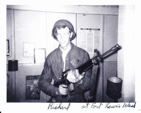 Richard Reins poses with a gun at Fort Lewis, Wash.