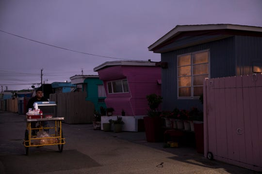 In this Monday, Sept. 3, 2018, photo, a food vendor passes through a mobile home park, where the majority of tenants are farm workers, in Salinas, Calif. Few cities exemplify California's housing crisis better than Salinas, an hour's drive from Silicon Valley and surrounded by farm fields. It's one of America's most unaffordable places to live, and many residents believe politicians lack a grip on the reality of the region's housing crisis. (AP Photo/Jae C. Hong)