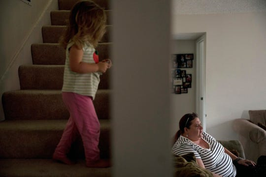 """In this Wednesday, Sept. 5, 2018, photo, middle-school English teacher Maryam Powers sits on her sofa as her 2-year-old daughter walks up the steps leading to the master bedroom in Salinas, Calif. Powers rents out the master bedroom for $800 a month to afford the mortgage on the three-bedroom home she purchased in 2015. """"I work, work, work, work, work. I take every extra pay job I can do, and I never quite get ahead,"""" Powers said one recent evening after school. (AP Photo/Jae C. Hong)"""