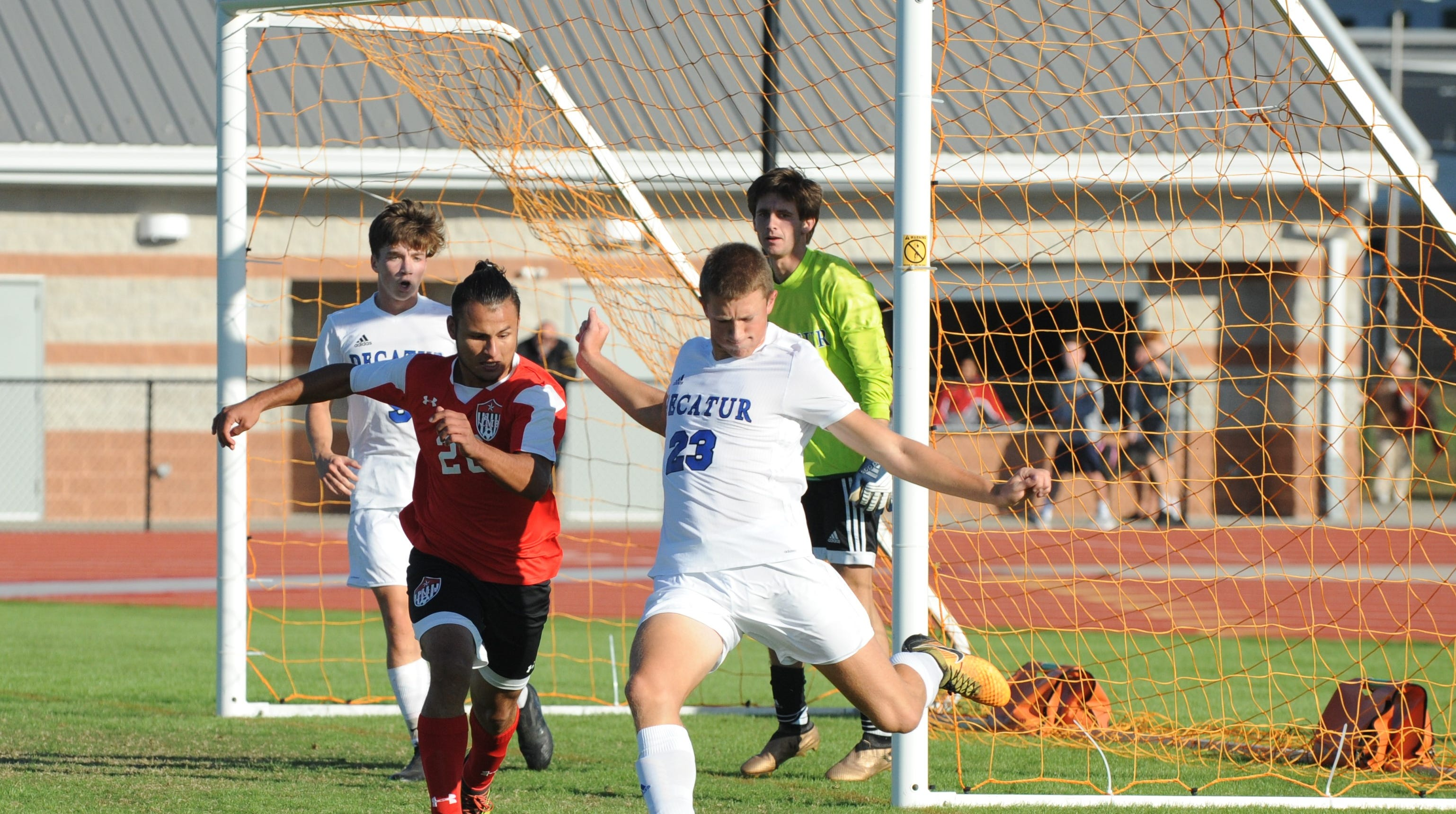 Decatur's Drew Haueisen tries to clear the ball from the goal against Bennett in Bayside South soccer action Oct. 17, 2018.