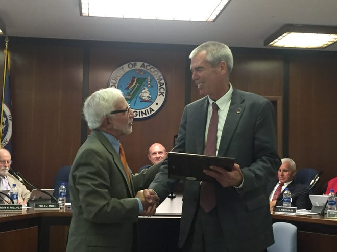 Accomack County Supervisor Ron Wolff, left, presents a resolution commemorating NASA's 60th anniversary to Bill Wrobel, NASA Wallops Flight Facility director, in Accomac, Virginia on Wednesday, Oct. 17, 2018.