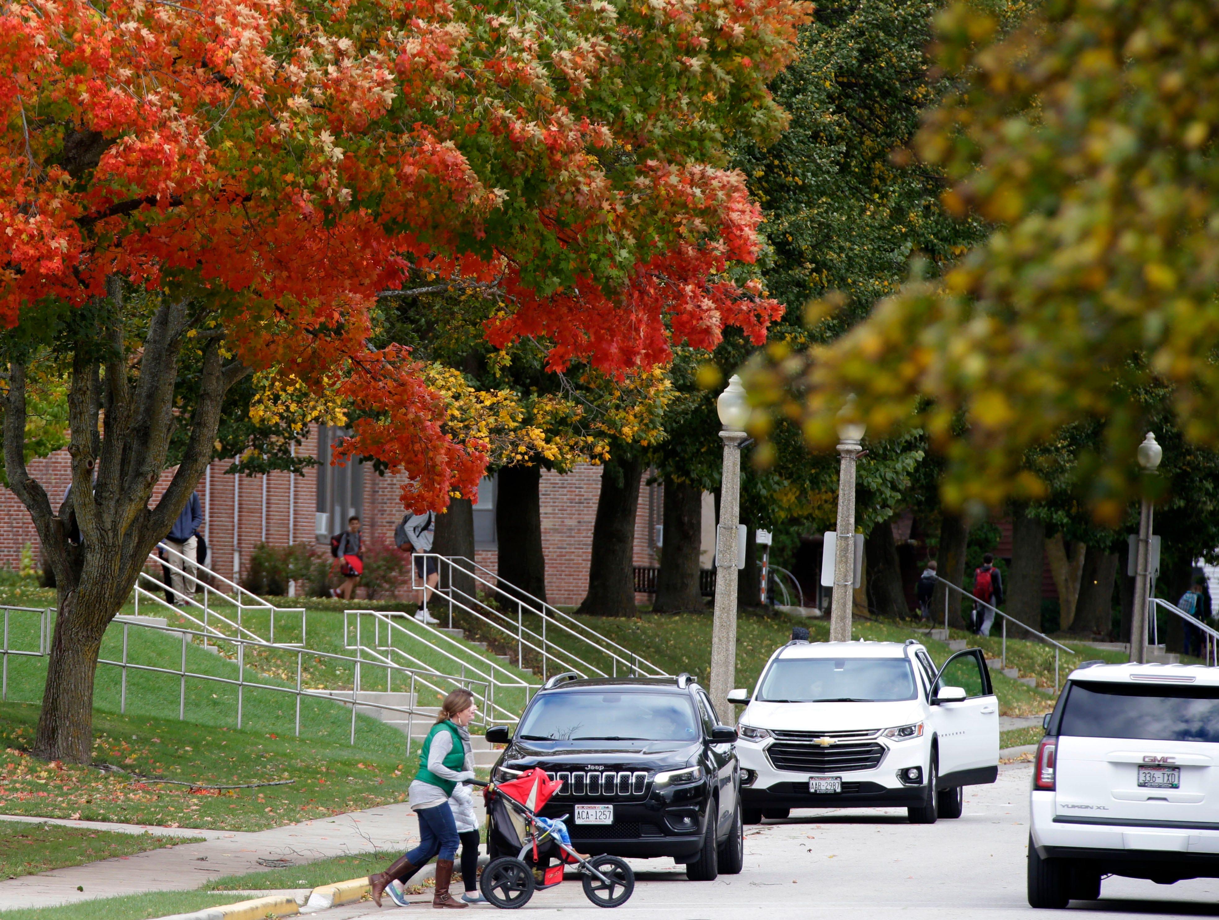A woman crosses School Street near Kohler Schools, Thursday, October 11, 2018, in Kohler, Wis.