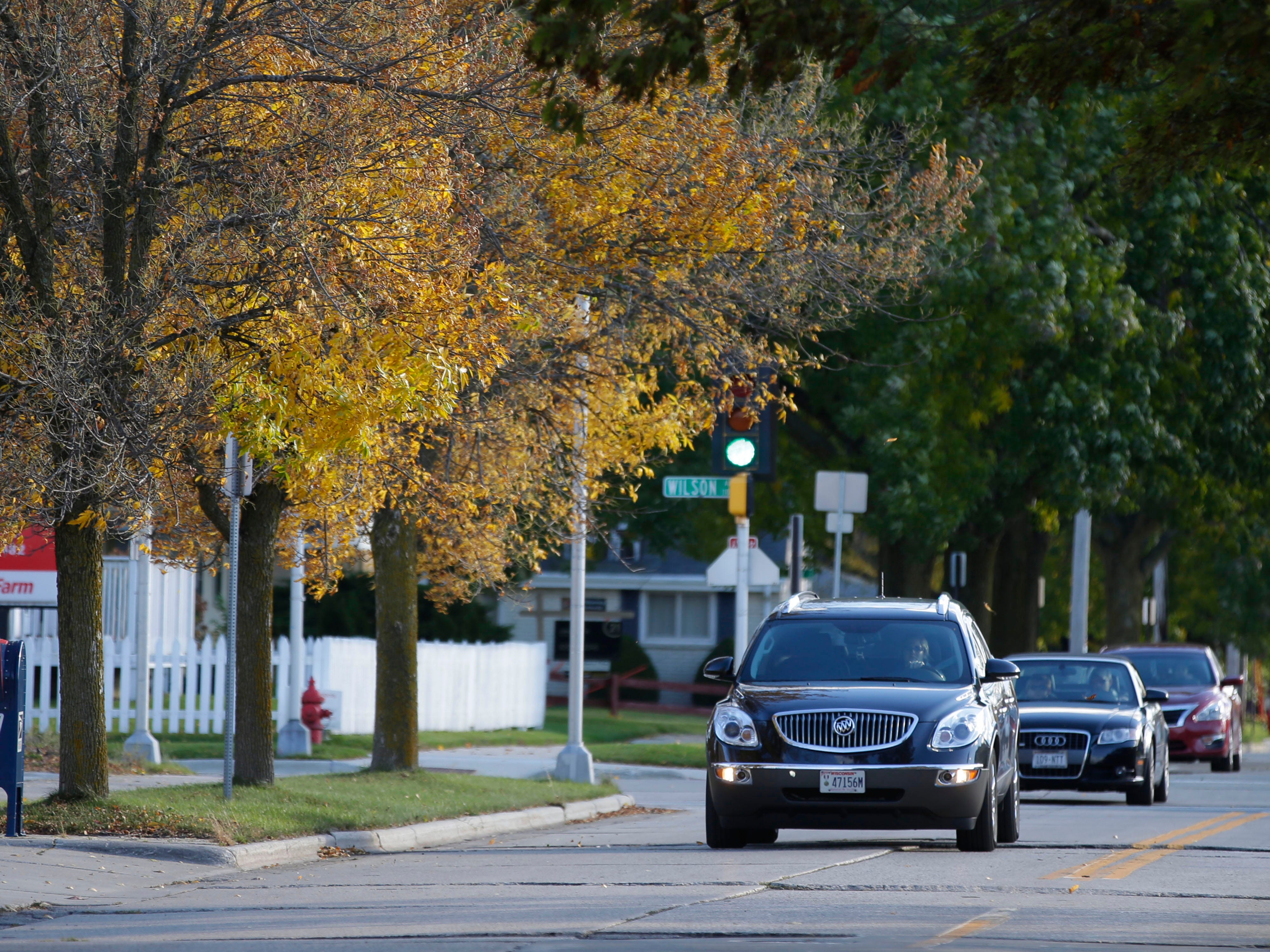 Cars drive along the changing colors of South 12th Street, Monday, October 15, 2018, in Sheboygan, Wis.