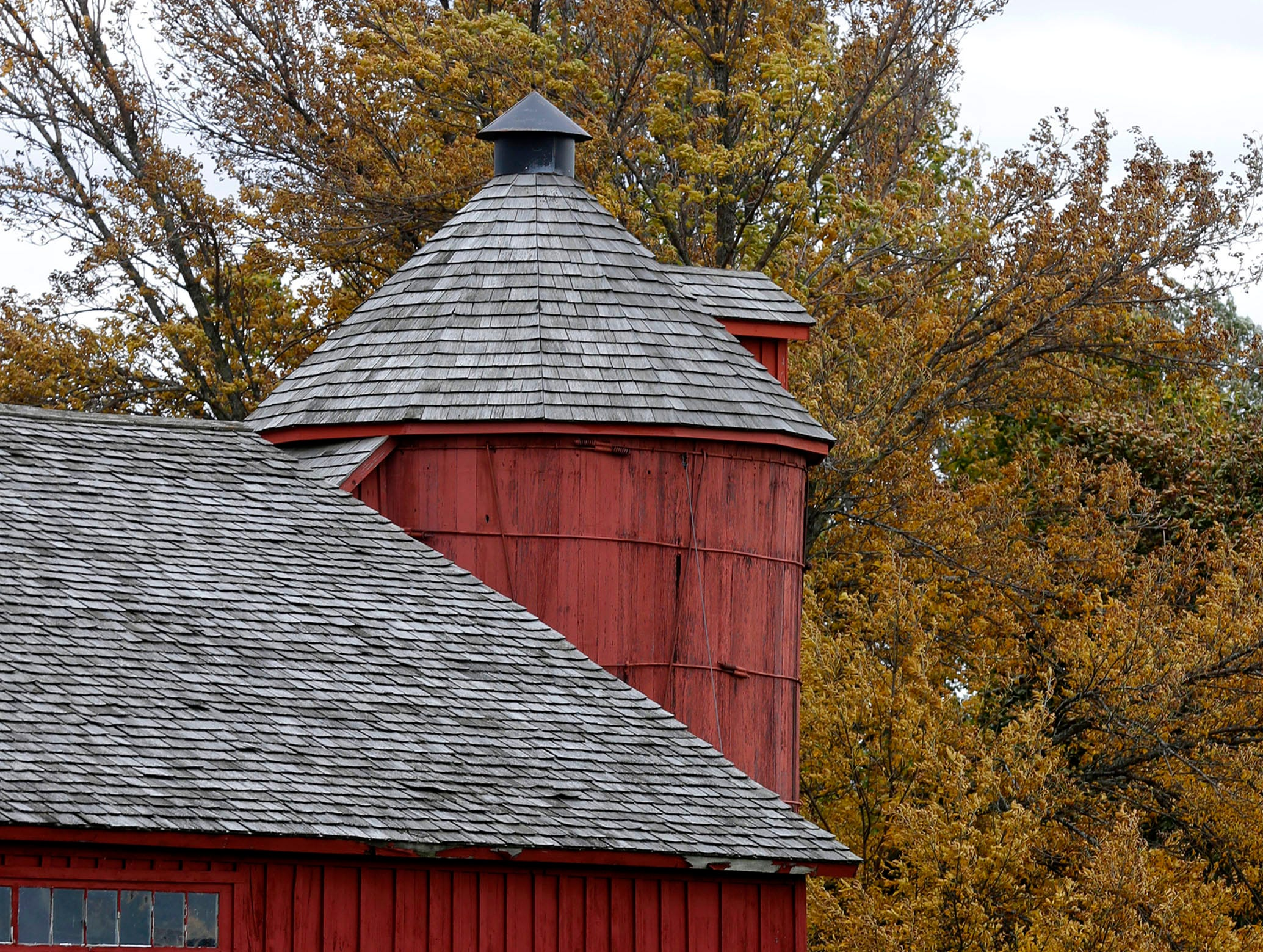 The barn at the Sheboygan County Historical Museum contrasts with trees turning color, Thursday, October 11, 2018, in Sheboygan, Wis.