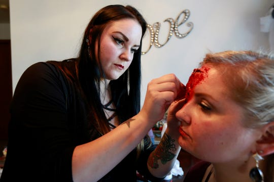 Make-up artist Lacey Radomski, 29, left, works on an effects on her 33-year-old sister Melissa Radomski's face Wednesday, Oct. 18, 2018, at her house in Plover, Wis.