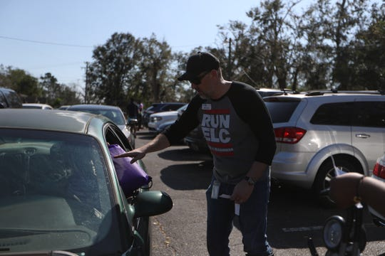 Matt Guse, CEO of the Early Leaning Coalition of the Big Bend Region, hands out supplies for children to Gadsden County residents in the parking lot of the ELC office in Quincy, Fla. during an emergency response distribution Thursday, Oct. 18, 2018. The distribution event was organized as a partnership between the ELC and Save the Children organization.