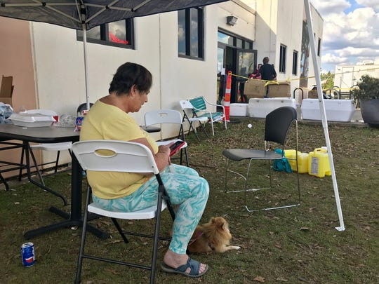"Pam Estrada and her Pomeranian ""Little Bit"" rest outside the Mossy Pond Public Library and Community Center on Wednesday."