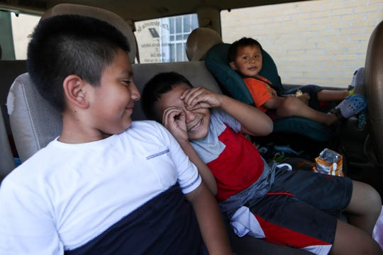 Antonia Perez, 6, center goofs around with his brothers Armando, 9, left and Alfonso, 2, in the back seat of the family's van driven by their sister Amalia Perez, 18, as the family waits in line at the Early Learning Coalition of the Big Bend office in Quincy, Fla. during an emergency response distribution event Thursday, Oct. 18, 2018. The distribution event was organized as a partnership between the ELC and Save the Children organization.