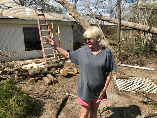 Myrtle Young examines damage to her home and property Wednesday in Clarksville.