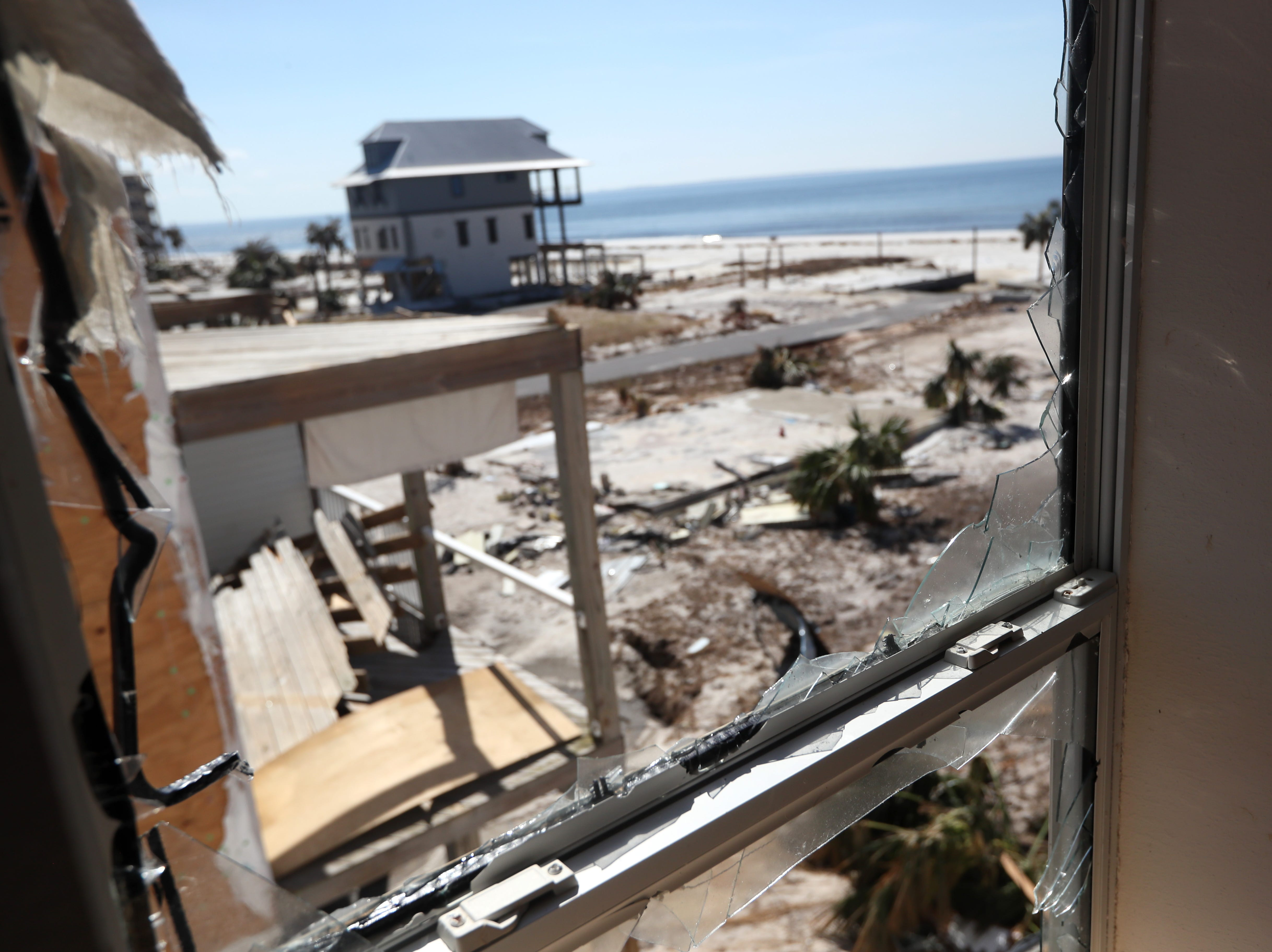 A wind-damaged beach front can be seen through a broken window in the Higdon family condo in Mexico Beach on Wednesday, Oct. 17, 2018, one week after Hurricane Michael ripped through the coastal Florida town.
