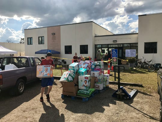 People load up supplies Wednesday outside the Mossy Pond Public Library and Community Center, which is serving as a public shelter and supply spot.