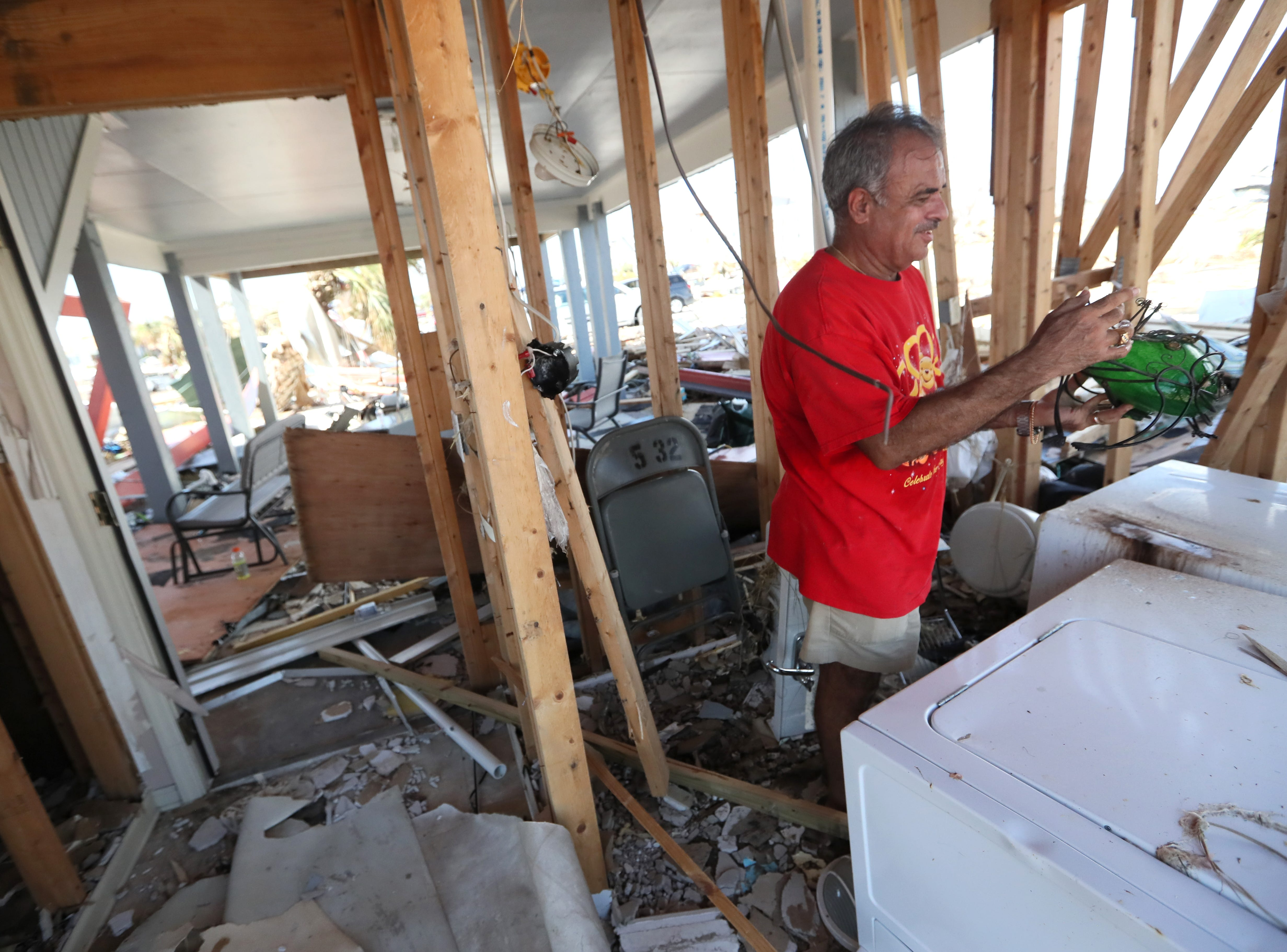 Jaques Sebastiao smiles as he finds a glass frog sculpture he saved from his neighbors yard, still intact, inside of his demolished Mexico Beach home on Wednesday, Oct. 17, 2018, one week after Hurricane Michael ripped through the coastal Florida town. Sebastiao moved in to the home fulltime with his with wife Bela just two months ago.