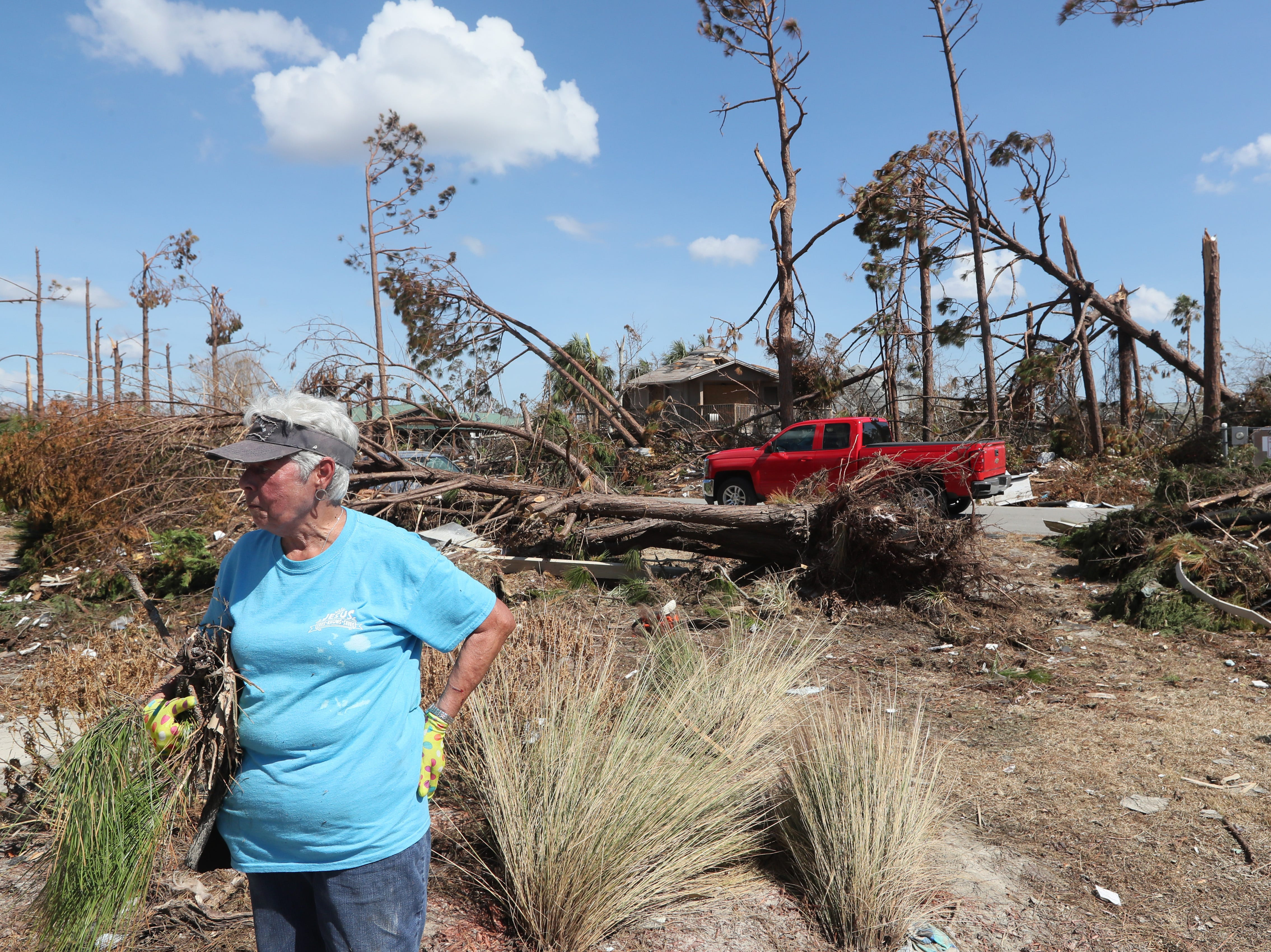 Barbara Redd works to clear the yard of debris at their family vacation home in Mexico Beach on Wednesday, Oct. 17, 2018, one week after Hurricane Michael ripped through the coastal Florida town.