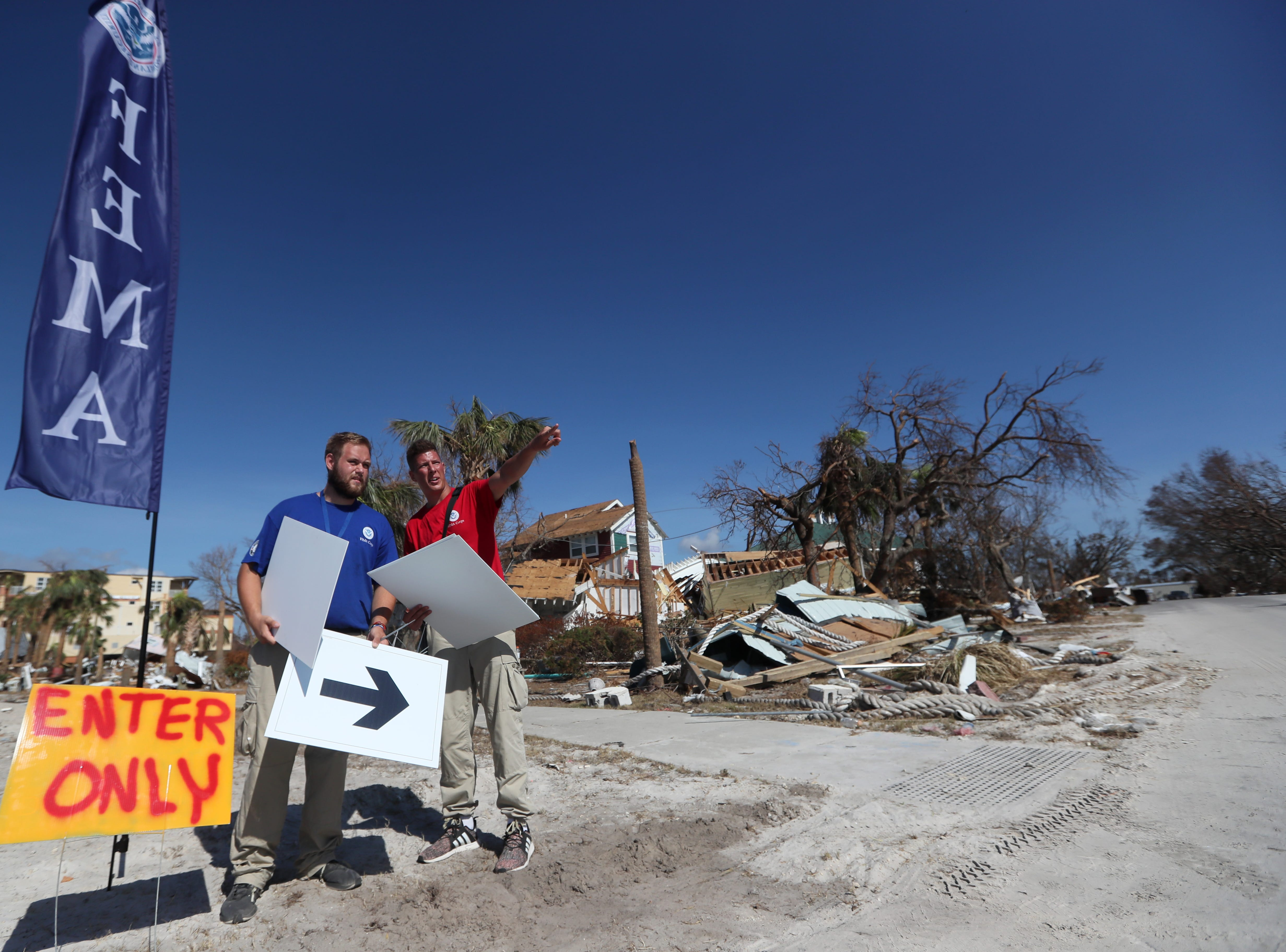 FEMA workers Edward Epperson, left, and Alex Unger plot their path to meet residents in Mexico Beach on Wednesday, Oct. 17, 2018, one week after Hurricane Michael ripped through the coastal Florida town.