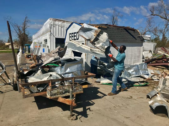 Workers clean up the tin roof blown off the Clarksville general store on Highway 20.