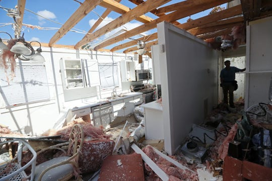 Insurance inspector Ryan Rhoades looks over the Mexico Beach home of the Redd family on Wednesday, Oct. 17, 2018, one week after Hurricane Michael tore the roof off and flooded the home as it ripped through the coastal Florida town.