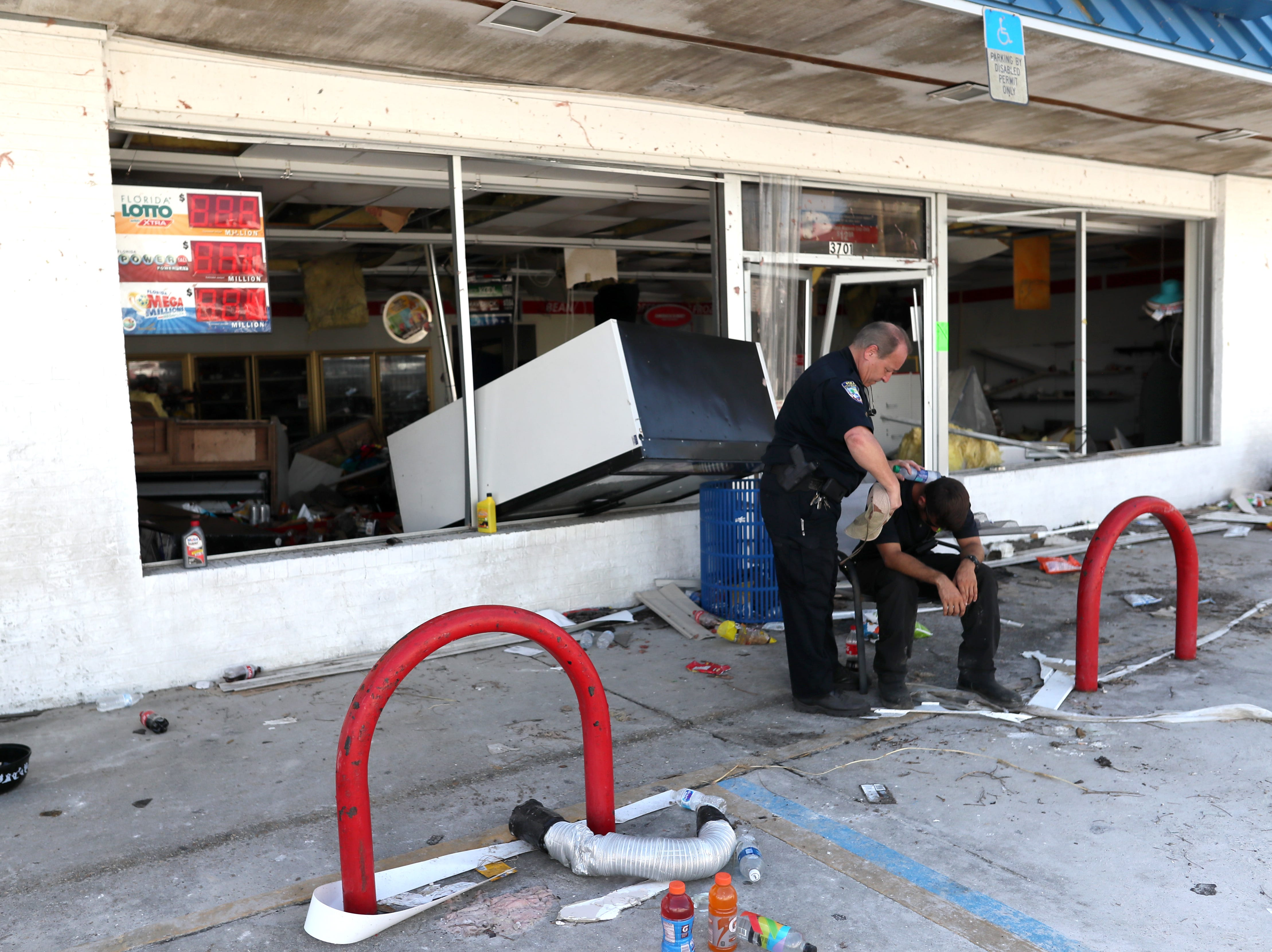 Police Chief Anthony Kelly helps to cool down a fellow first responder after feeling faint in Mexico Beach on Wednesday, Oct. 17, 2018, one week after Hurricane Michael ripped through the coastal Florida town.