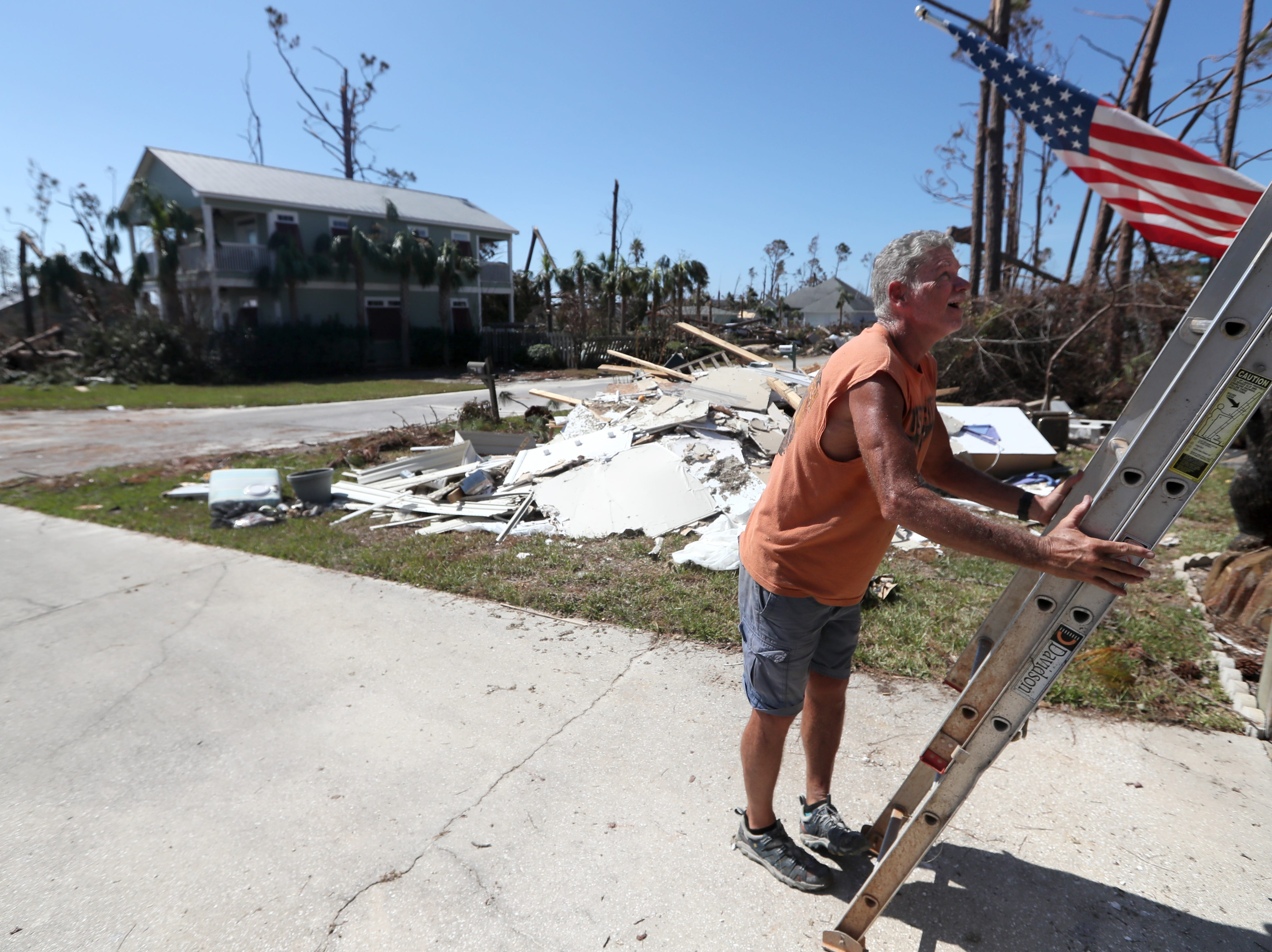 Mexico Beach resident Rick Barnes adjusts a ladder which he now uses to access what is left of his second-floor home, which was left destroyed on Wednesday, Oct. 17, 2018, one week after Hurricane Michael ripped through the coastal Florida town.