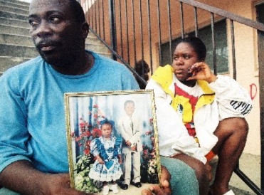 Odalbert Louise (left) and Neirva Dumerci, James Willie Tellasmon's uncle and cousin, sit outside the boy's home in Gifford Monday. Louise holds a photograph of Tellasmon and his 4-year-old sister, Karen Renard.