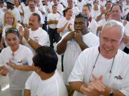 VERO BEACH - Ronald Barron, center, whistles as Bob Allen, bottom right, and fellow Piper Aircraft, Inc., employees cheer after the official announcement from president and CEO Jim Bass that the company will be staying in Vero Beach. Also on hand for the announcement was Governor Charlie Crist.